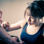 Image of female tattooist working on an arm